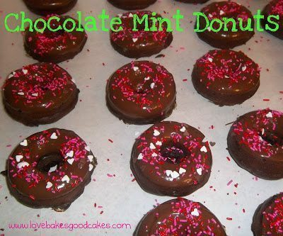 Chocolate mint donuts with pink and white sprinkles on wax paper