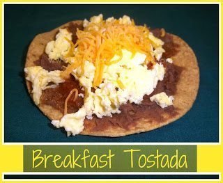 Breakfast tostada with refried beans, eggs and shredded cheese on plate