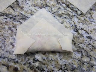 Uncooked pizza roll being folded in half again on counter top