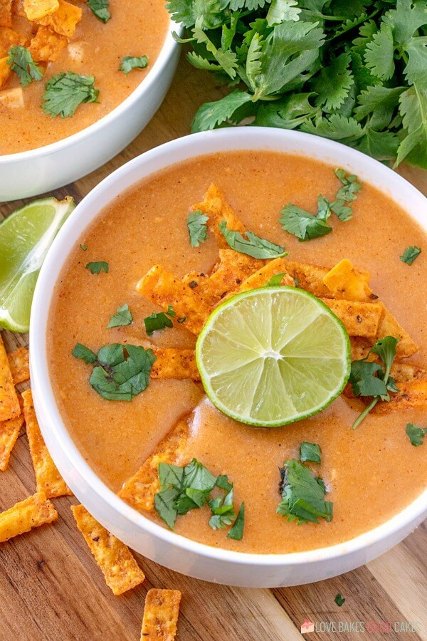 Chicken Enchilad Soup in bowl garnished with cilantro, tortilla strips, and lime