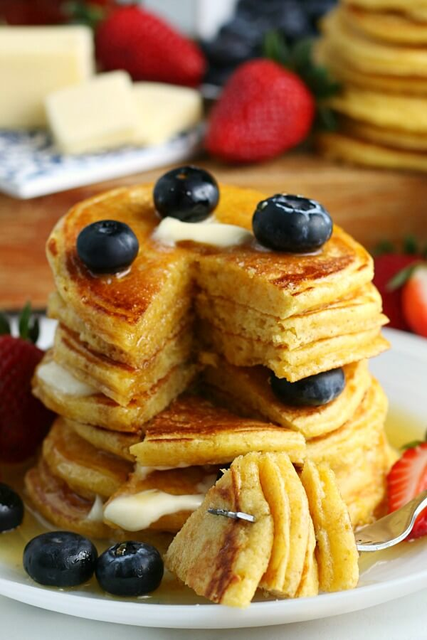 stack of cornbread pancakes with bite cut out on fork