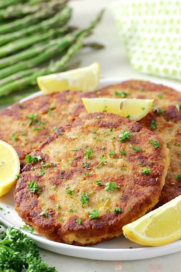 Salmon Patties on a plate with lemon wedges.