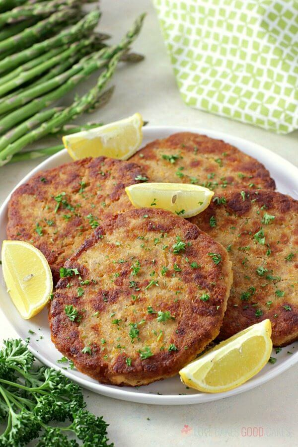 Salmon Patties on a plate with lemon wedges and fresh vegetables.