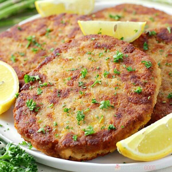 Salmon Patties on a plate with lemon wedges close up.