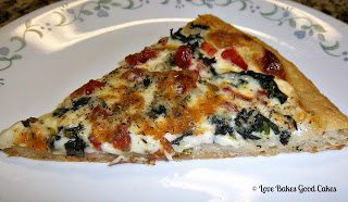 Tomato Spinach Alfredo Pizza slice on white plate