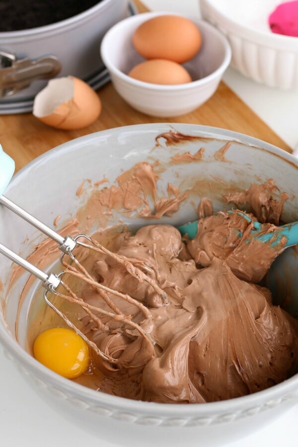 Adding eggs to the Chocolate Bliss Cheesecake ingredients in a mixing bowl