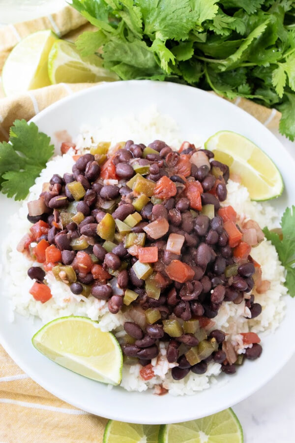 overhead view of cuban black beans and rice on white plate with lime wedges