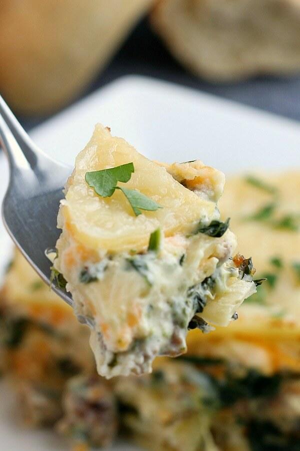 bite of spinach alfredo lasagna on fork