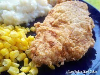 Southern Fried Chicken piece with mashed potatoes and corn on blue plate close up