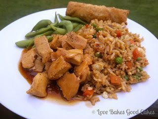 Spicy-Sweet Chinese Chicken with Asian snap peas and egg roll on white plate.