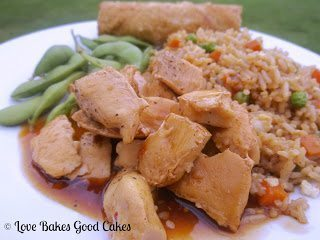 Spicy-Sweet Chinese Chicken with Asian snap peas and egg roll on plate.