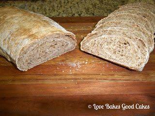 Rustic Triple Apple Bread loaf cut in half on cutting board