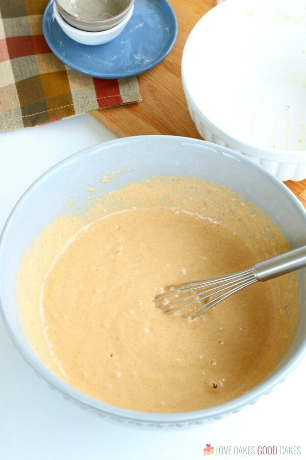 Pumpkin and milk and eggs whisked together for a pumpkin pancake recipe.