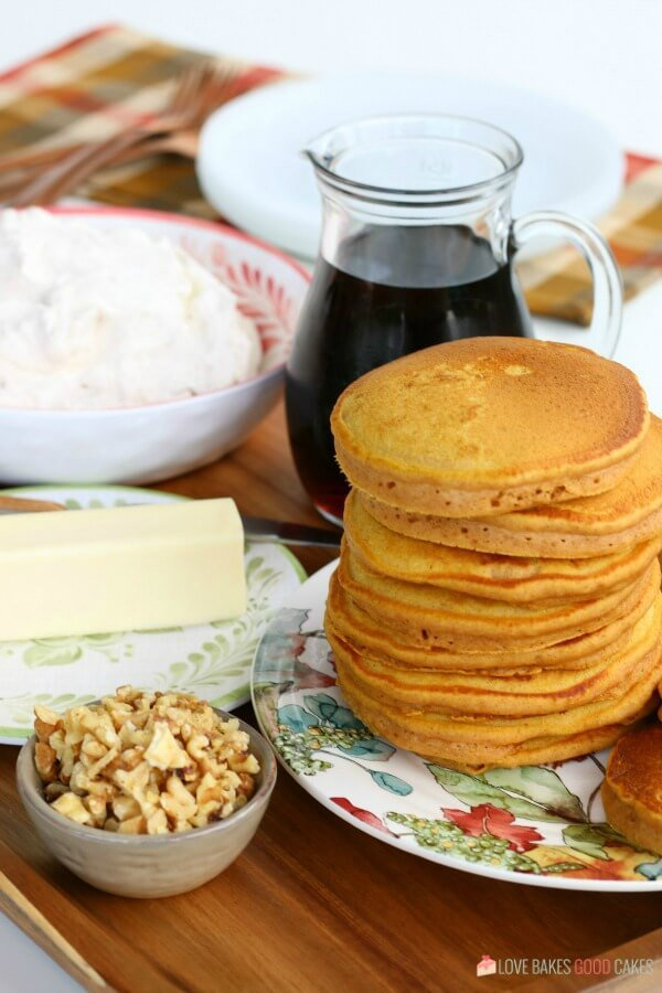 Pumpkin pancakes stacked up on a plate with a bottle of syrup and a bowl of nuts.