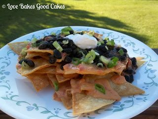Black Bean Nachos with chives and sour cream on white plate.