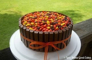 Kit-Kat Cake with reeses pieces on top with bow on white cake stand.