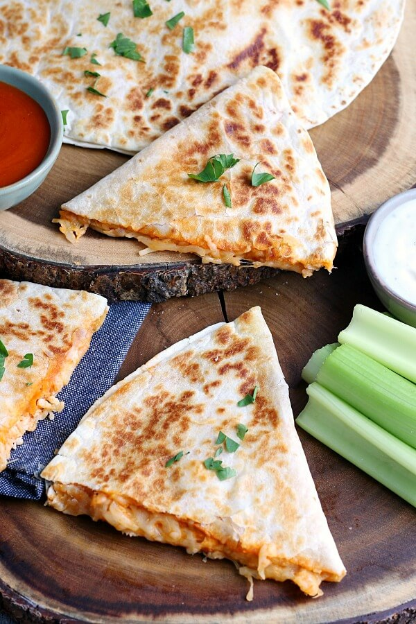 A top down view of the finished quesadillas with buffalo sauce, ranch, and celery for dipping!