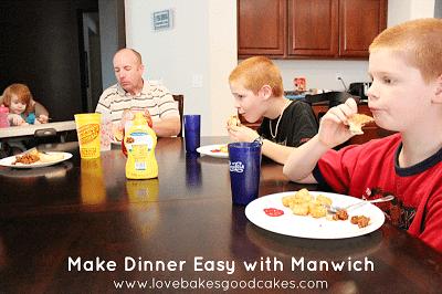 Family sitting around the table eating sloppy joe's.