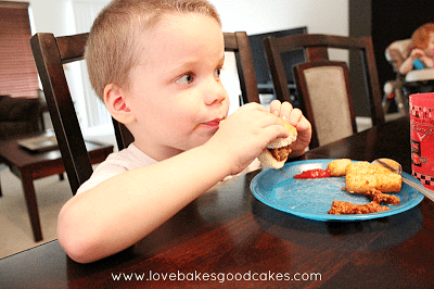 Boy sitting at the table eating sloppy joe's.