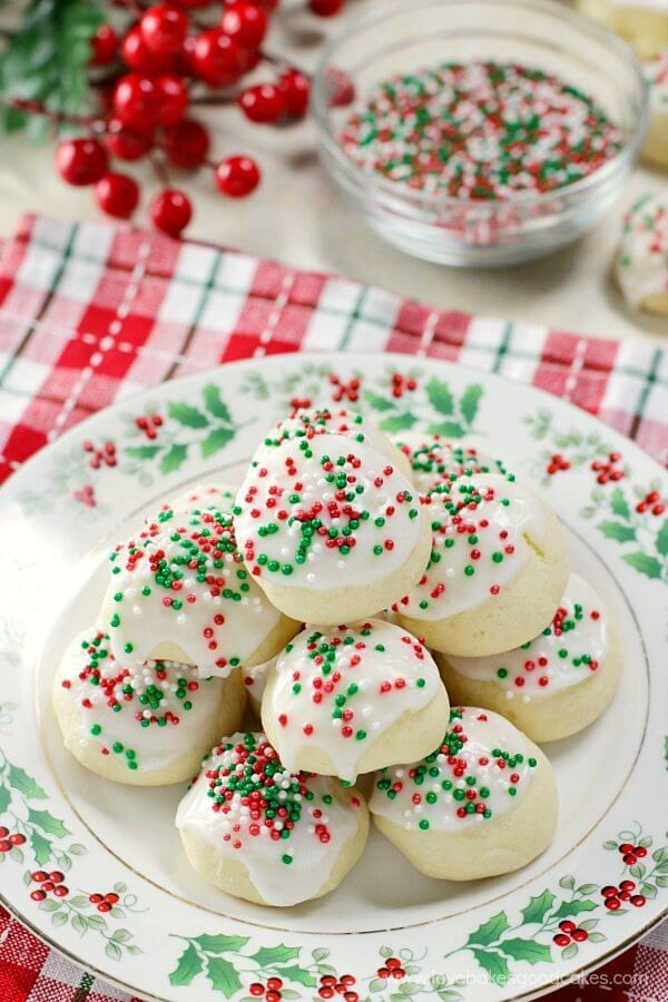 Italian Anise Cookies stacked up on plate with bowl of red and green sprinkles in background.