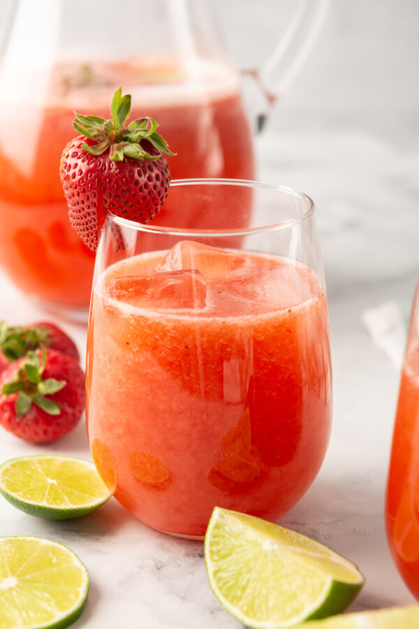 glass of strawberry agua fresca garnished with a strawberry