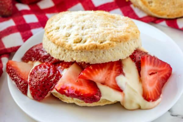 closeup of strawberry shortcake with lemon cream sauce on plate