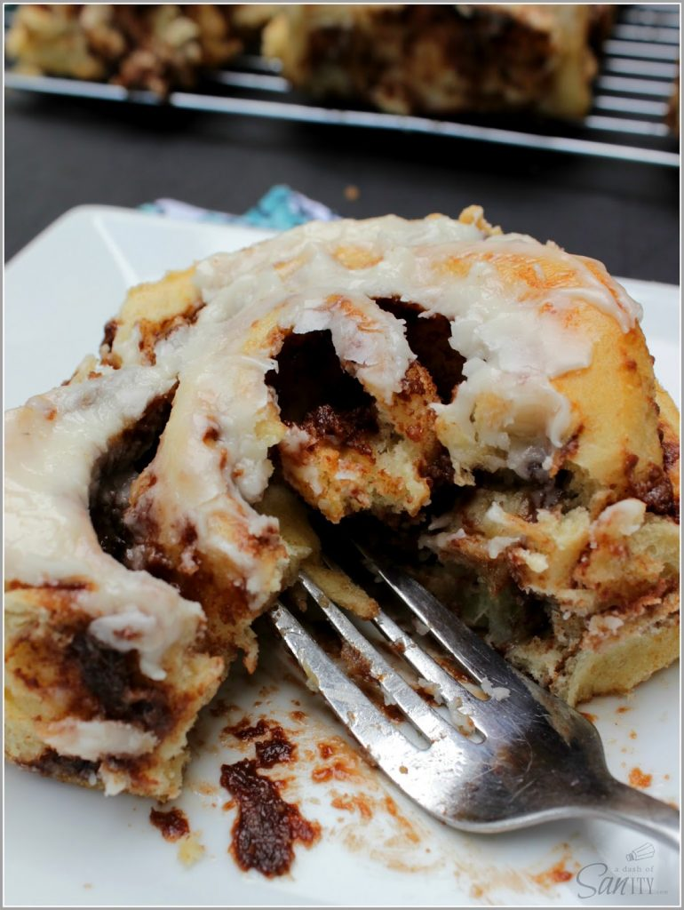 Nutella Banana Cinnamon Roll on a plate with a bite removed.