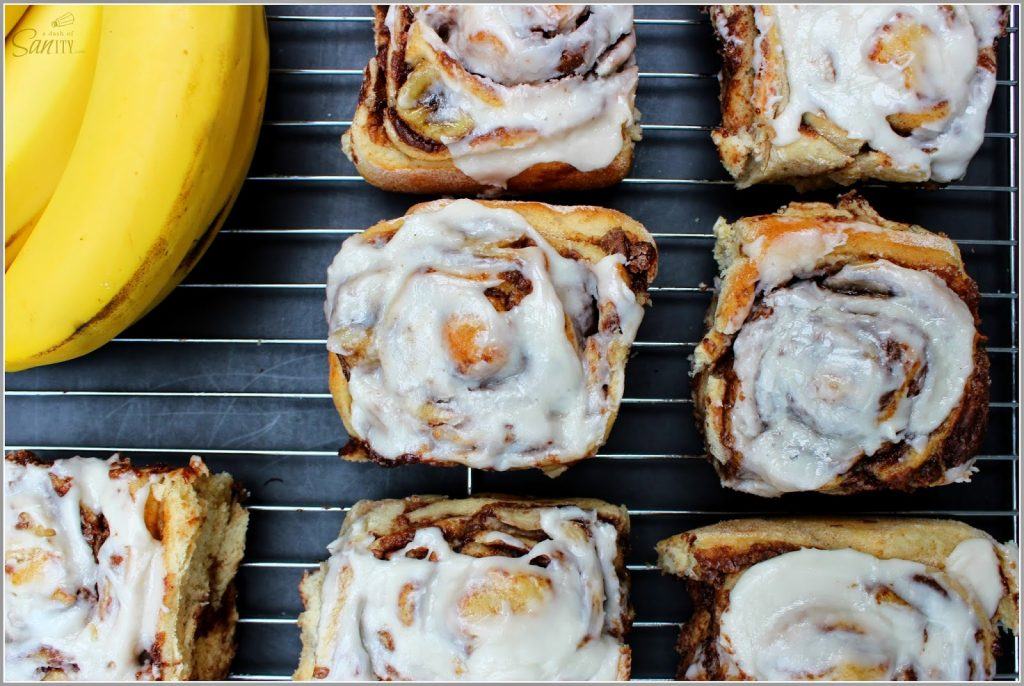 Nutella Banana Cinnamon Rolls on a cooling sheet with bananas.