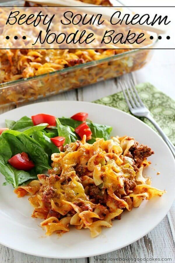 Beefy Sour Cream Noodle Bake on a plate with a green salad and a fork.
