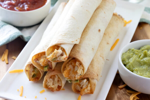 jalapeno popper chicken taquitos on white plate