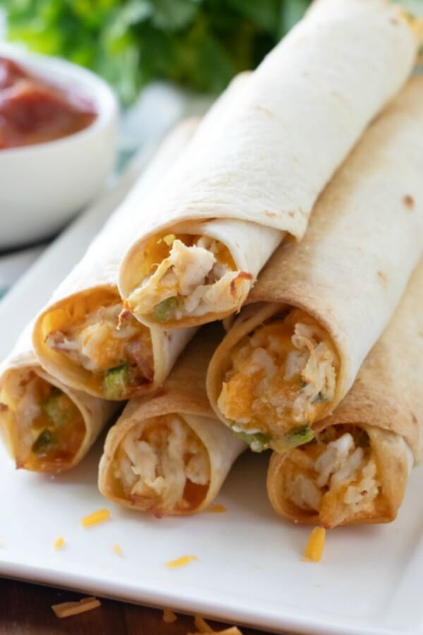 Jalapeno Popper Chicken Taquitos on white plate with salsa in background