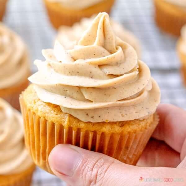 Pumpkin Cupcake with Pumpkin Spice Cream Cheese Frosting being held in hand.