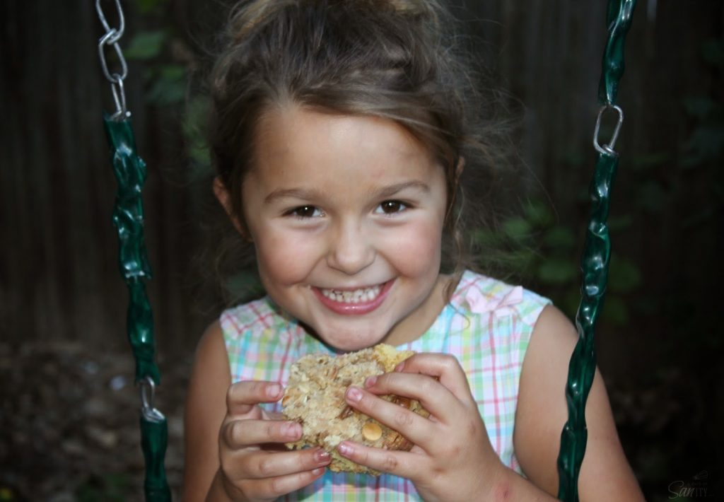 Girl eating a piece of White Chocolate Raspberry Crumb Cake on a swing.