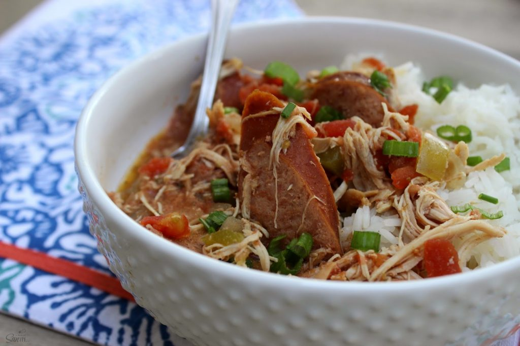 Slow Cooker Chicken and Sausage Gumbo in a white bowl with a spoon.