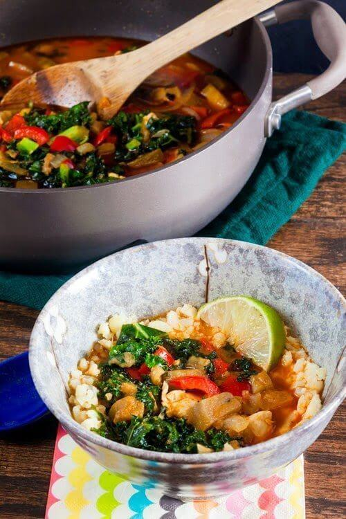 """Red Curry Eggplant and Kale Over Cauliflower """"Rice"""" in a pan and bowl."""