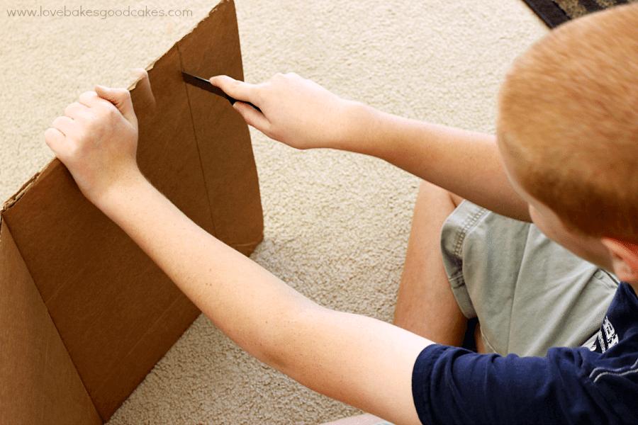 A boy cutting a cardboard box.