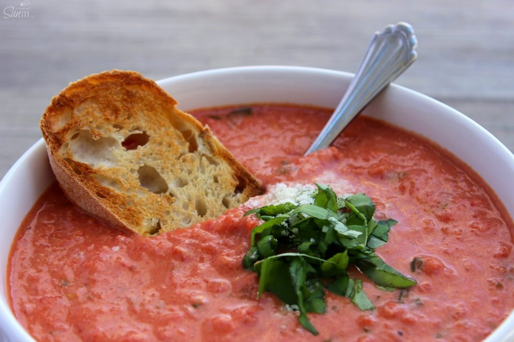 Light Creamy Tomato Bisque in a bowl with a piece of garlic toast and a spoon.