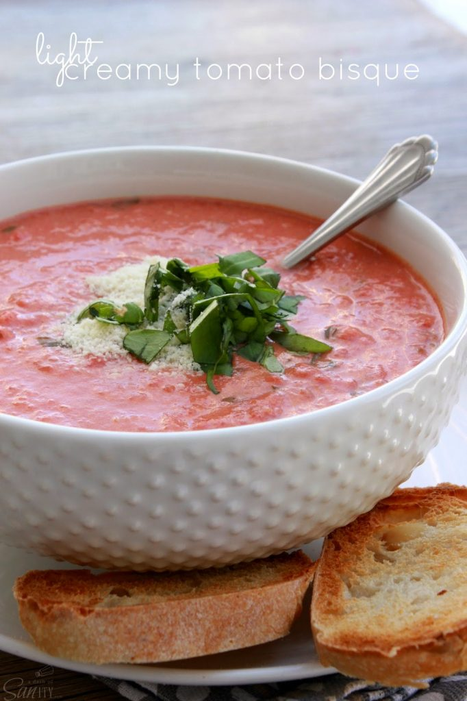 Light Creamy Tomato Bisque in a white bowl with a spoon and garlic toast.