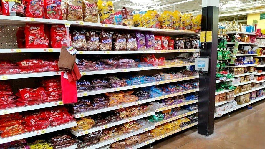A grocery store isle with candy on the shelves.