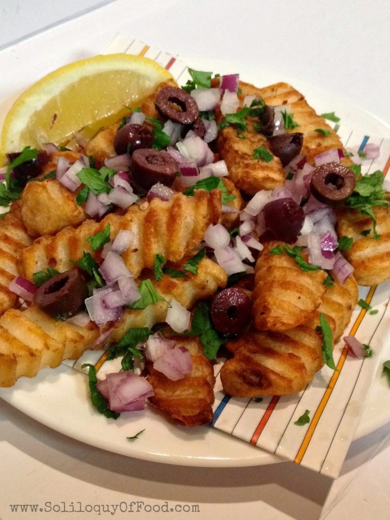 Greek Fries on a plate with a lemon.