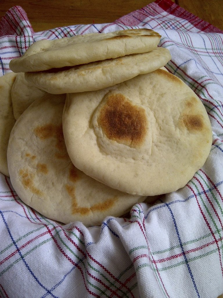 Greek Pitas stacked up in a bowl.