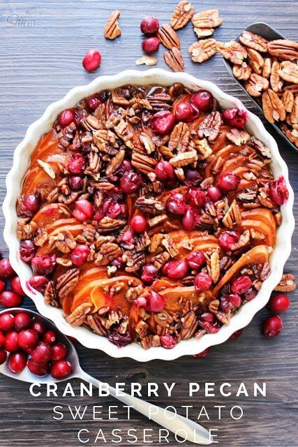Cranberry Pecan Sweet Potato Casserole in a white casserole dish with a spoon.