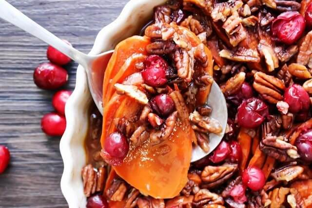 Cranberry Pecan Sweet Potato Casserole close up with a spoon.
