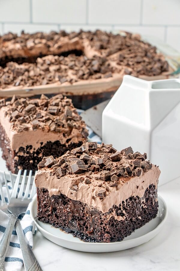chocolate poke cake slices on plates with cake pan in background