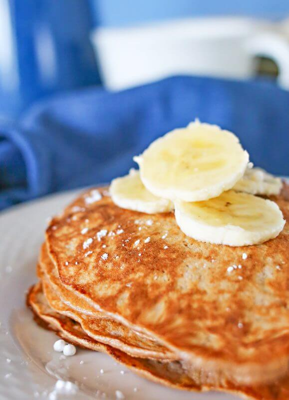 3 Ingredient Chocolate Protein Pancakes close up on a plate with banana slices.