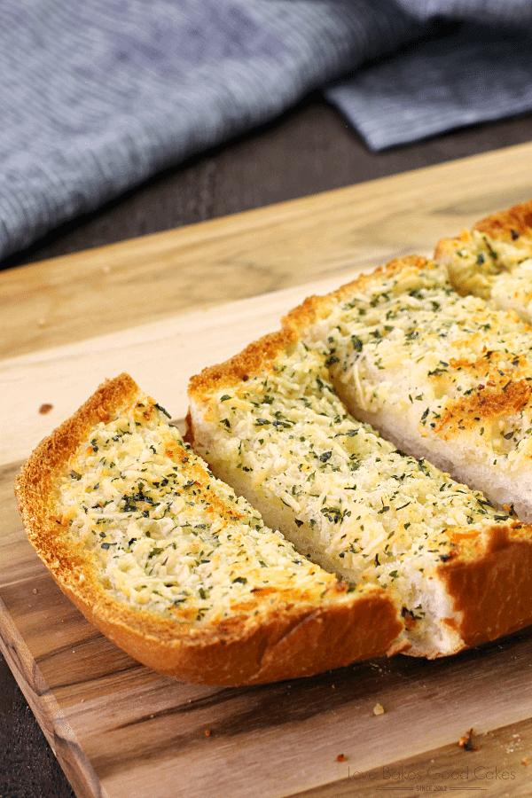 BEST Garlic Bread sliced on a cutting board close up.