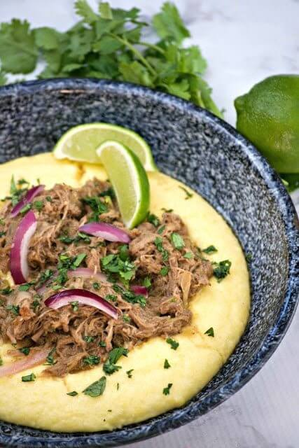 Slow Cooker Beef Chili Verde with Polenta in a bowl with fresh limes.
