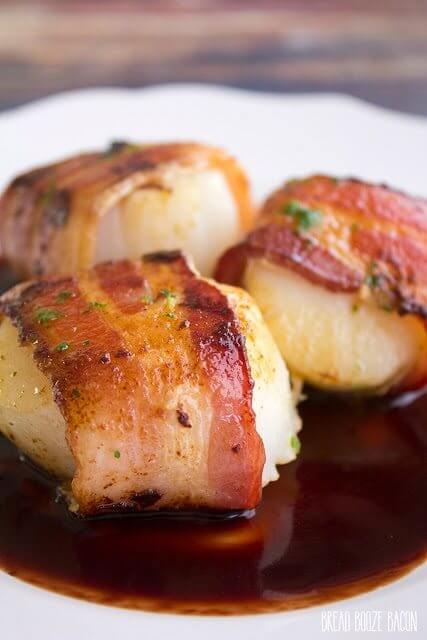 Bacon Wrapped Scallops in Pomegranate Sauce on a plate.
