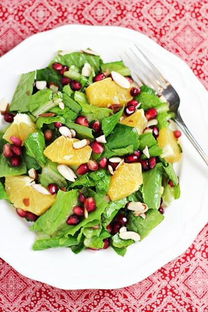 Orange and Pomegranate Salad on a white plate with a fork.