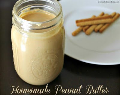 Homemade Peanut Butter in a glass jar with bread sticks on a white plate.